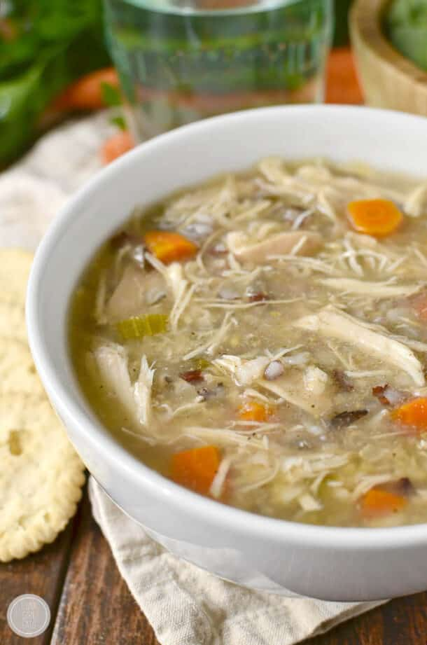 crockpot wild rice chicken soup in white bowl with crackers on the side
