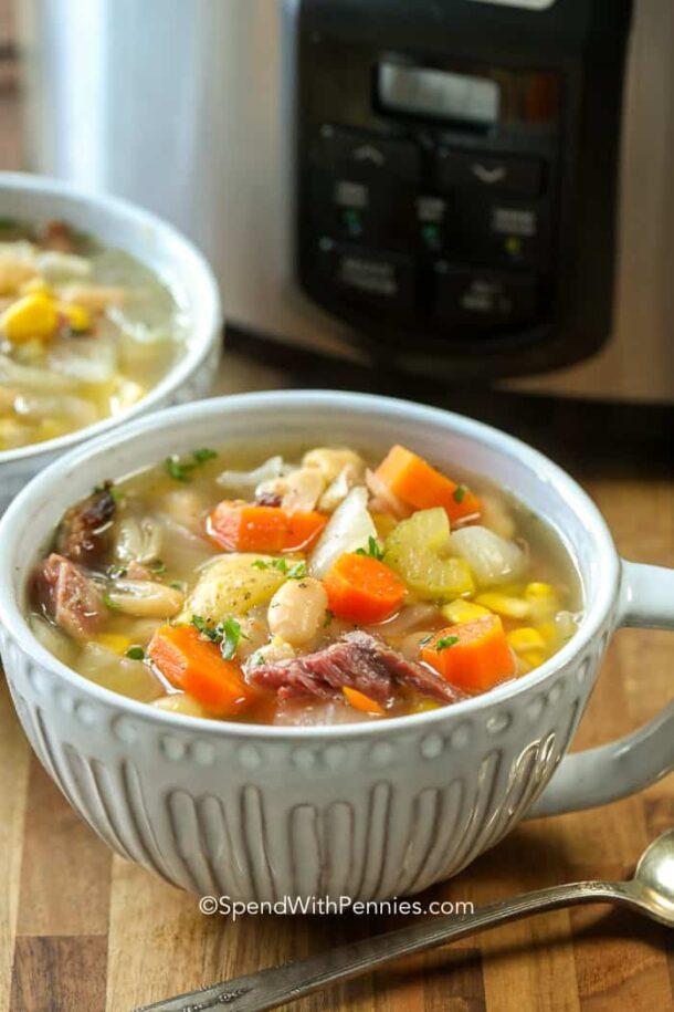 ham bone soup in grey soup mug in front of slow cooker