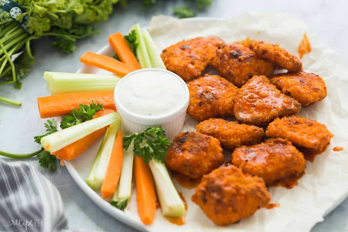 buffalo boneless chicken wings with celery and carrots and fresh parsley in the background