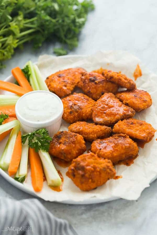 boneless chicken wings with buffalo sauce on white plate with carrots and celery sticks