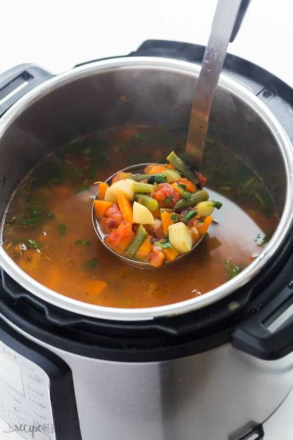 instant pot vegetable soup in pressure cooker with metal scoop scooping some out