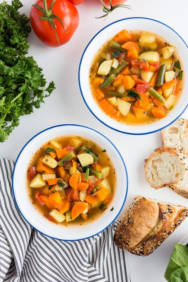 instant pot vegetable soup overhead in white bowls with fresh parsley and crusty bread on the side