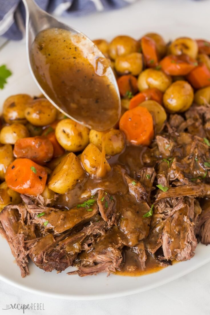 close up image of gravy being drizzled on slow cooker pot roast