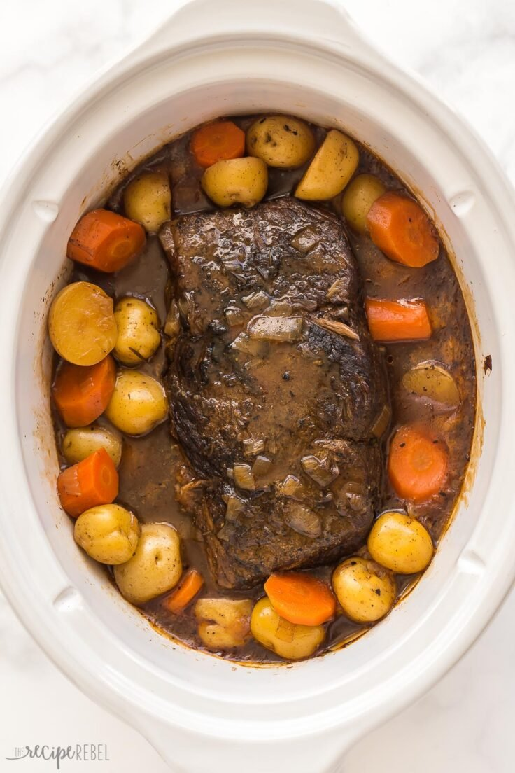 cooked slow cooker pot roast in white crockpot with potatoes and carrots