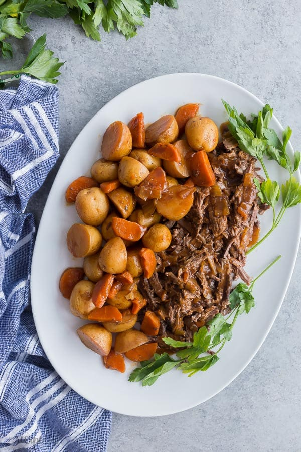 slow cooker pot roast on platter with potatoes and carrots and fresh parsley on a grey background