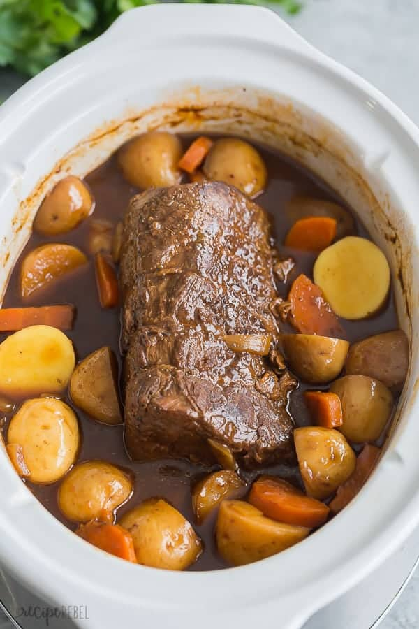slow cooker pot roast after cooking with potatoes and carrots and gravy