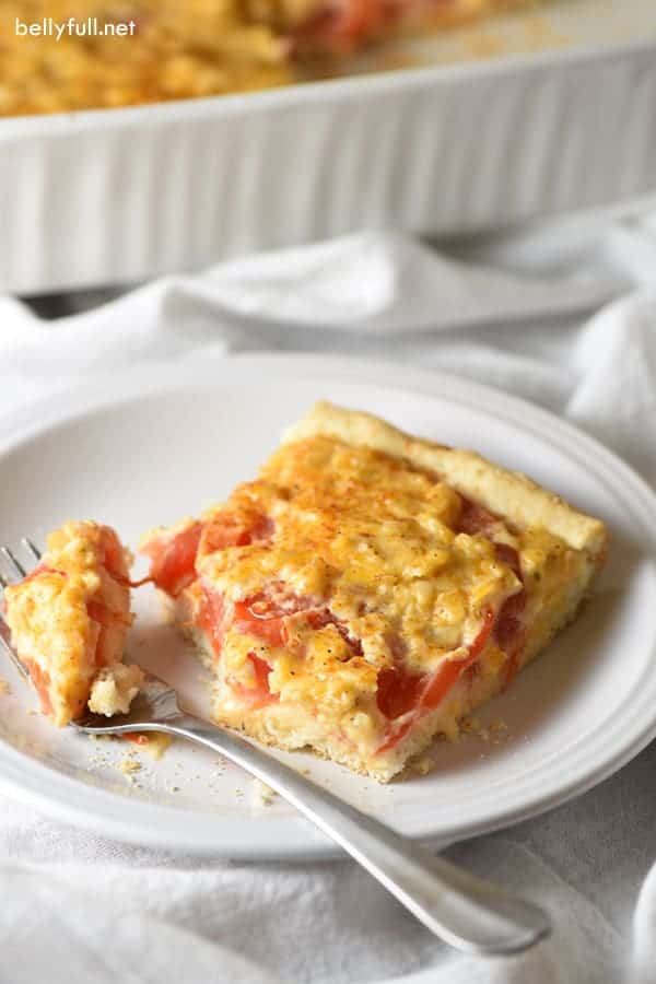 tomato biscuit casserole on white plate with fork taking a bite off the corner