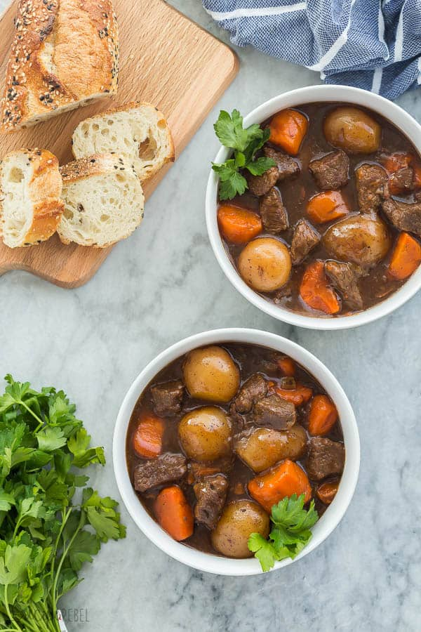 pressure cooker beef stew in white bowls overhead on grey marble background with crusty bread on the side