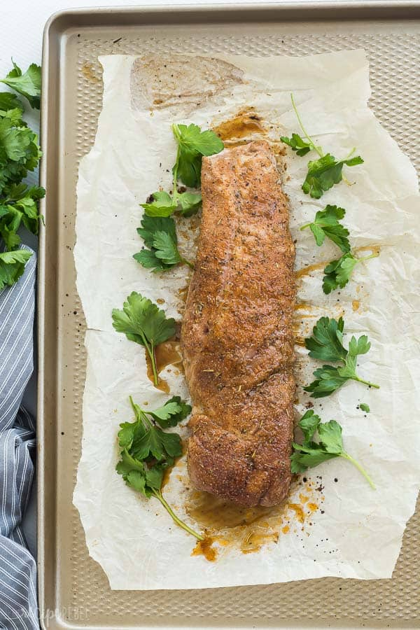roasted pork tenderloin whole on parchment lined baking sheet with fresh parsley garnish