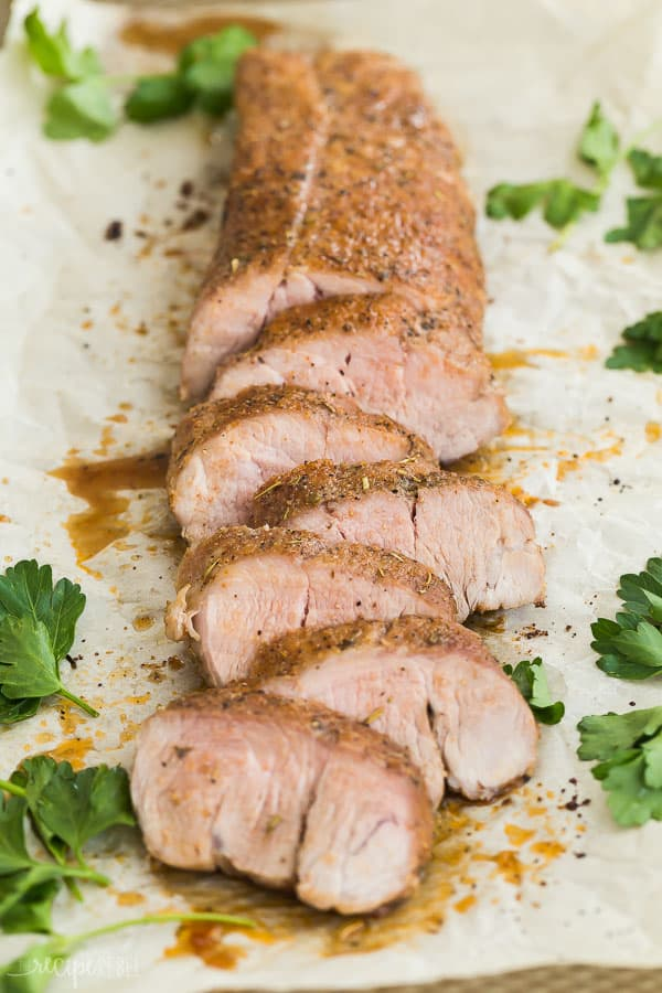 roasted pork tenderloin sliced on parchment with fresh parsley on the side