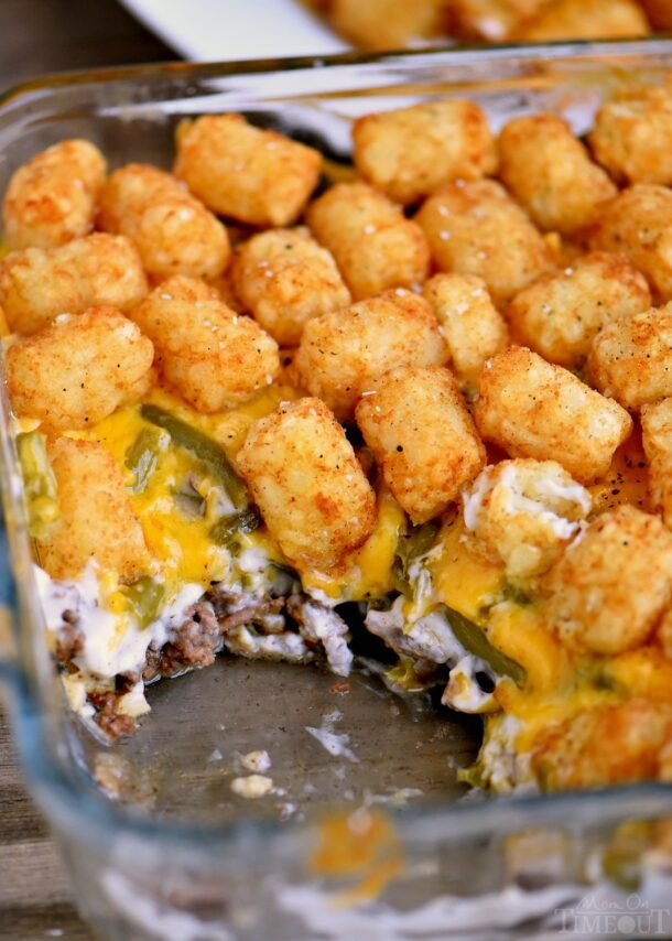 the best tater tot casserole in glass baking dish with a scoop missing