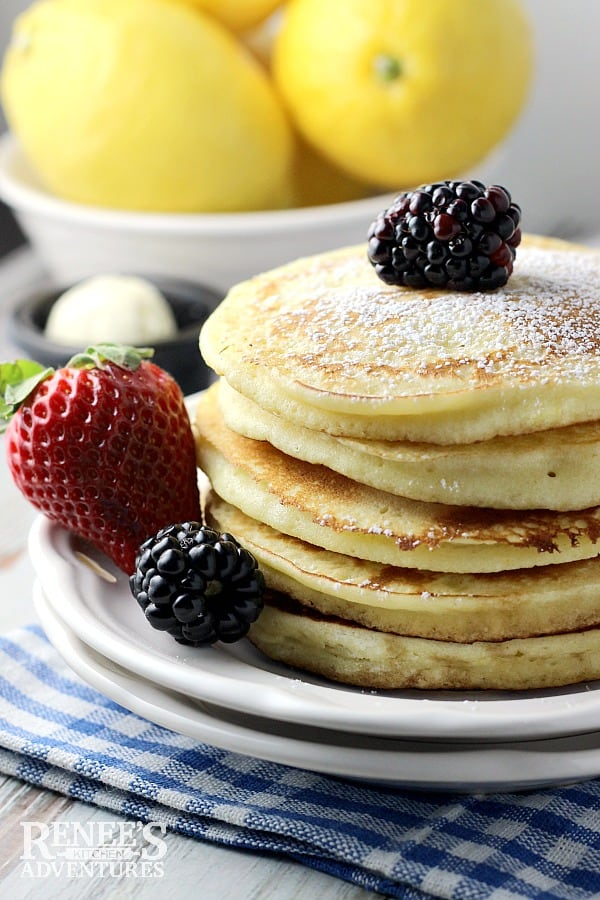 lemon ricotta pancakes stack with fresh blackberries and lemons in the background
