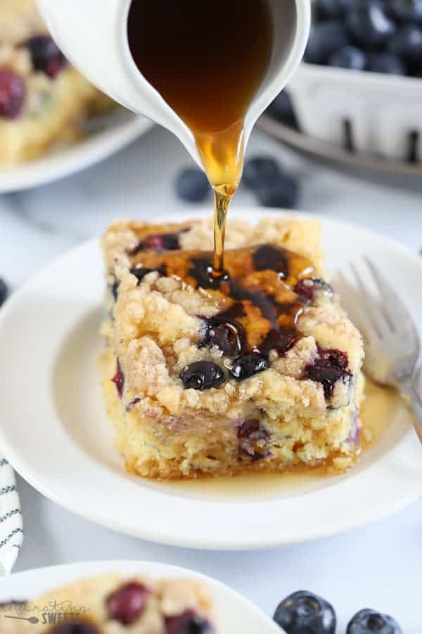 pancake casserole with blueberries and syrup being poured overtop