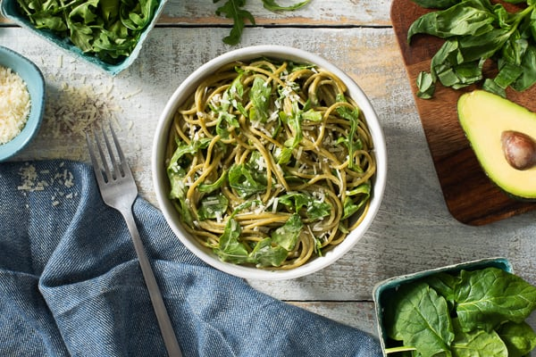 creamy greens pasta overhead in bowl with blue towel on the side
