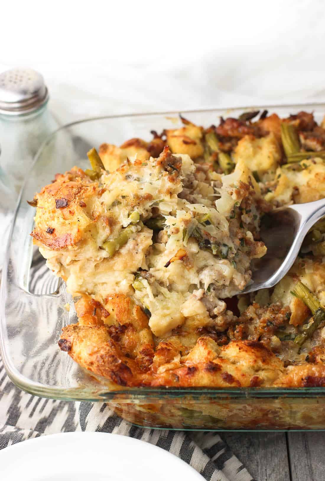 sausage strata with asiago and asparagus being scooped with metal spoon