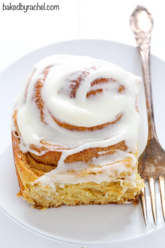 carrot cake cinnamon rolls on white plate with white background and frosting on top