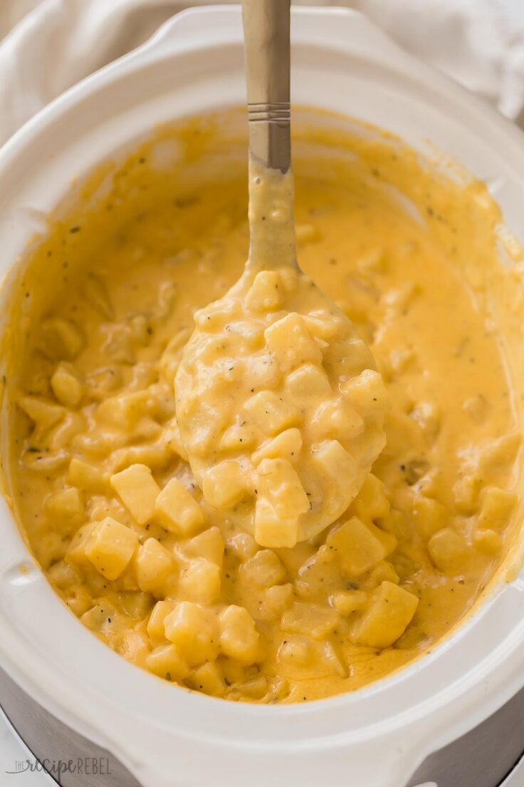 metal ladle lifting crockpot cheesy potatoes out of slow cooker