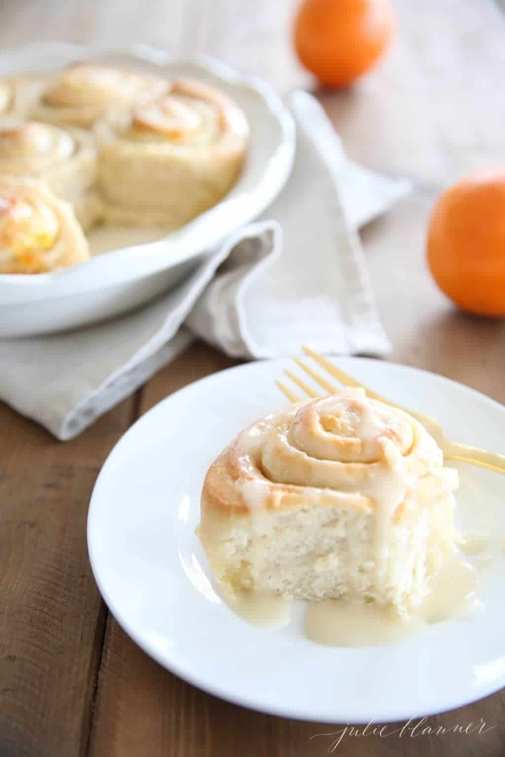 orange rolls with glaze on white plate and fork on the plate