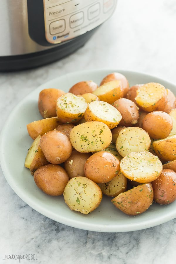 instant pot potatoes on blue plate on marble background with pressure cooker in the background
