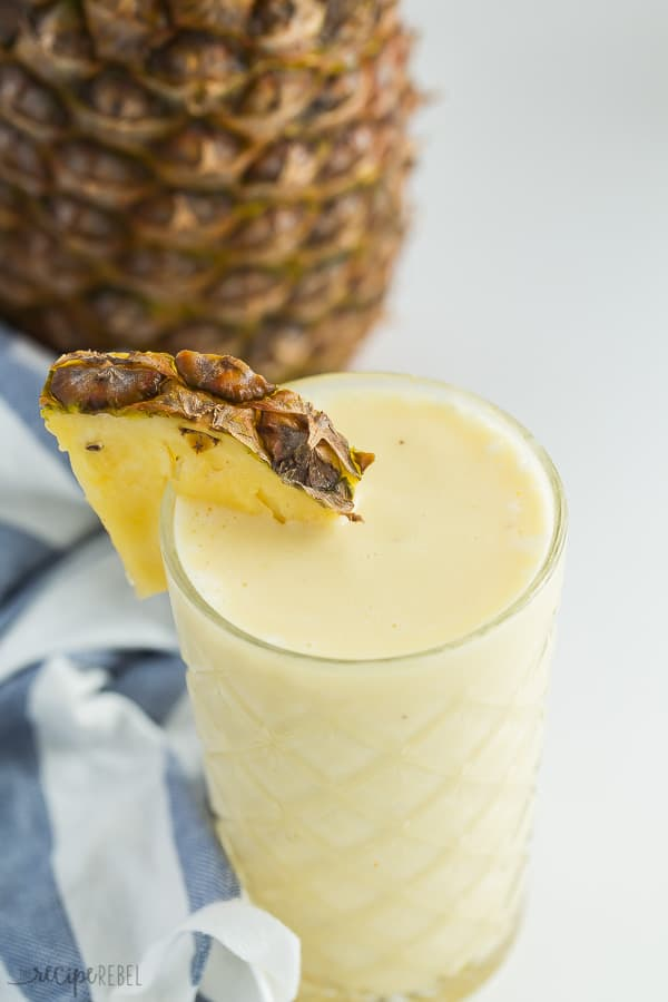 pineapple smoothie in tall glass with blue striped towel and whole pineapple in the background