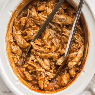 square image of crockpot bbq chicken with tongs