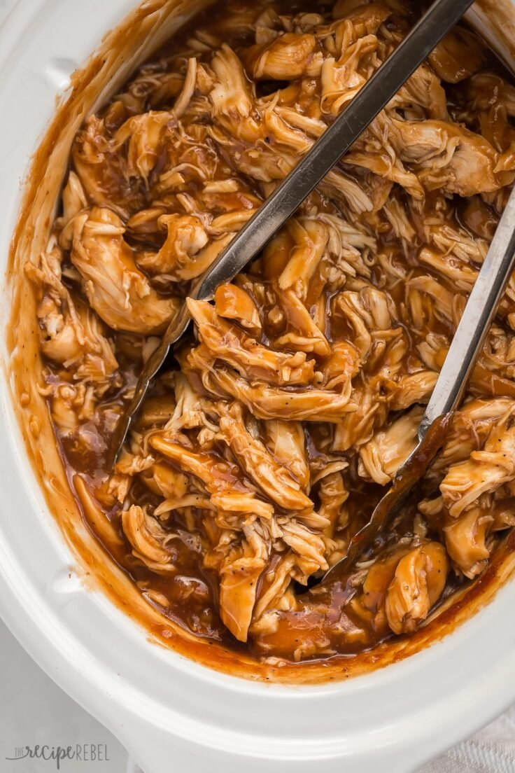 close up overhead image of slow cooker bbq chicken with tongs