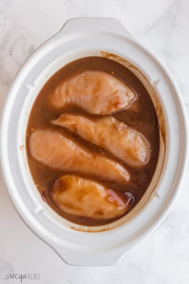 bbq sauce ingredients and uncooked chicken breasts in slow cooker