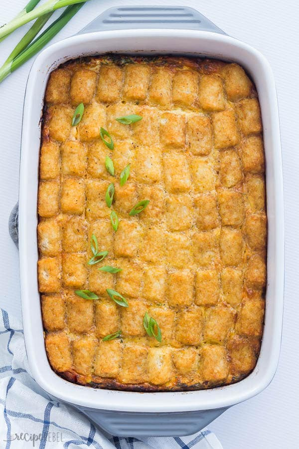 tater tot breakfast casserole in a white and grey baking dish overhead on white background