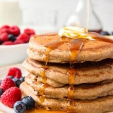 close up image of stack of four pancakes with syrup dripping down