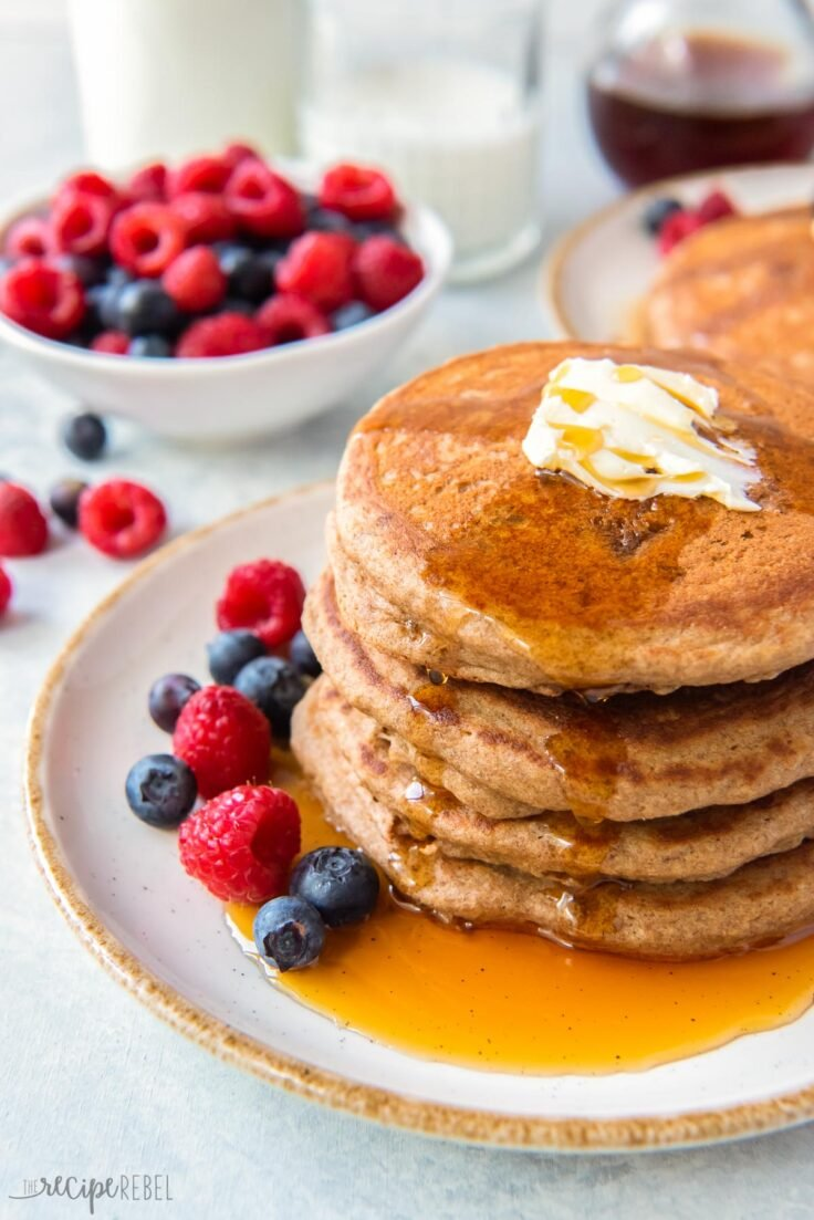 stack of pancakes on white plate with berries and syrup
