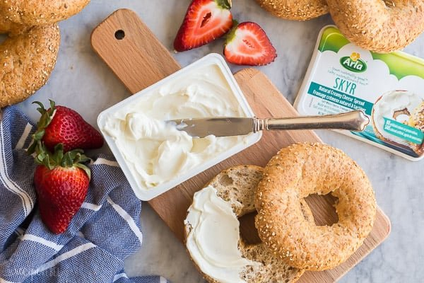 Arla cream cheese with bagel and knife stuck in cream cheese
