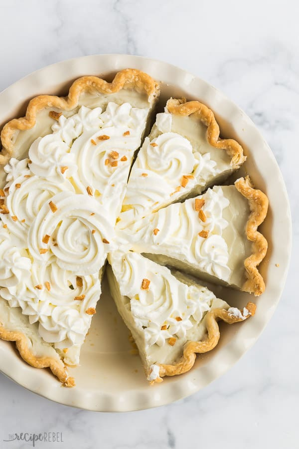 coconut cream pie whole with three slices in pan with toasted coconut