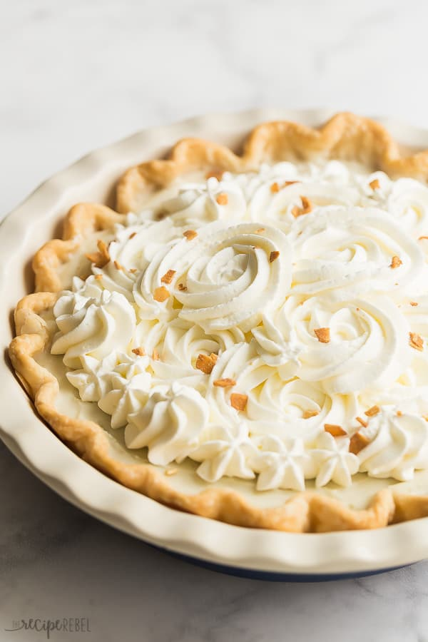 coconut cream pie whole with whipped cream roses on marble background