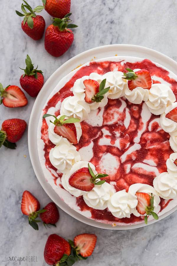 strawberry shortcake ice cream cake overhead with whipped cream and halved strawberries on grey marble background