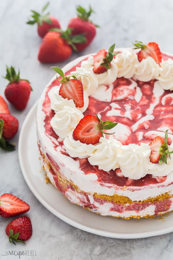 strawberry shortcake ice cream cake whole with whipped cream swirls and halved strawberries