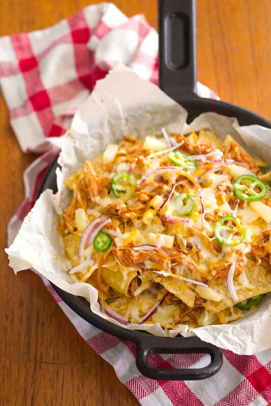 bbq chicken nachos in skillet on parchment paper on wooden table