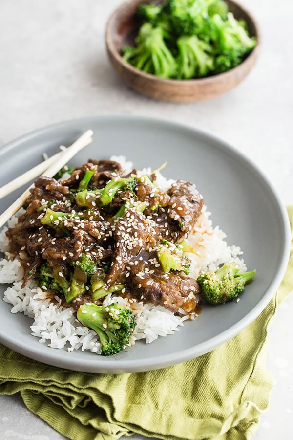 plate of Asian beef and broccoli over white rice on grey plate with broccoli in the background