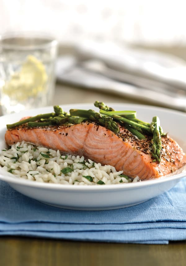 herbed salmon with asparagus on a plate of white rice on a blue towel