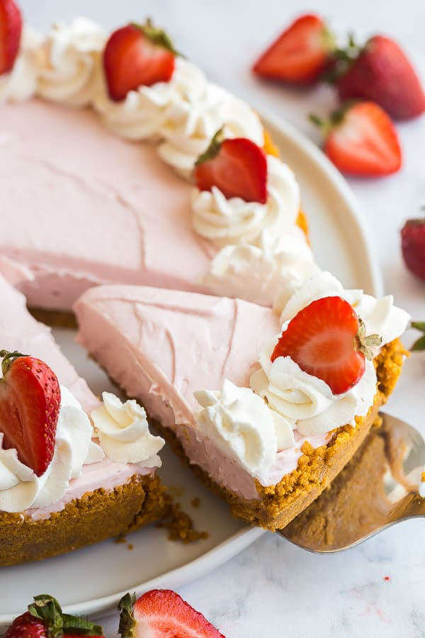 no bake strawberry cheesecake whole on white plate with piece being removed