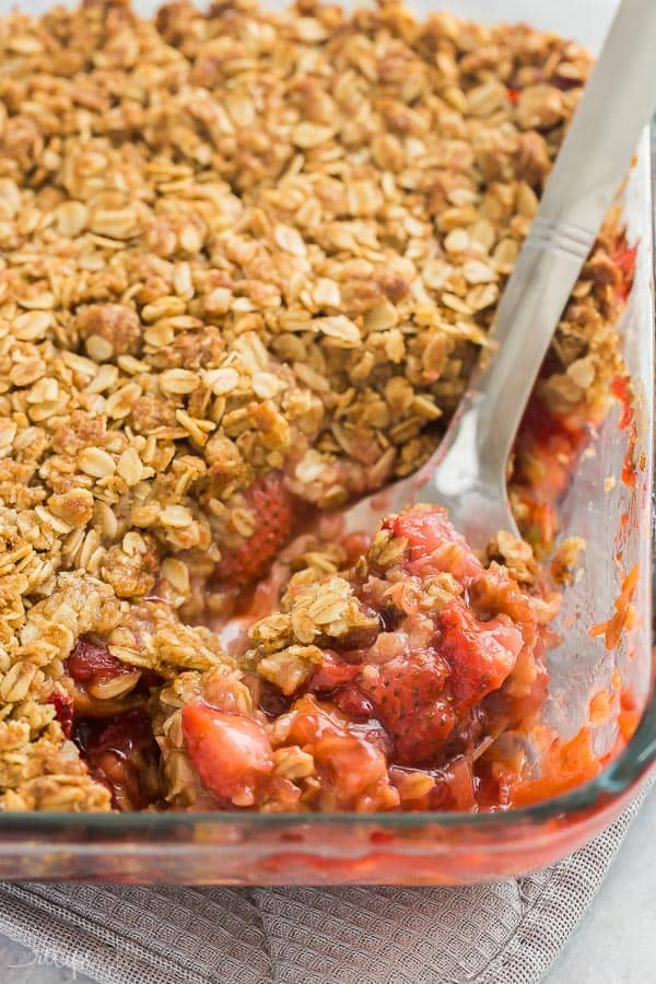 strawberry rhubarb crisp close up of scoop in glass baking dish