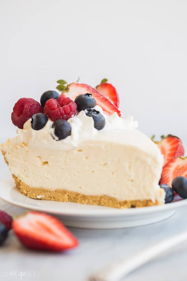 easy cheesecake recipe close up on white plate with fresh berries on white background