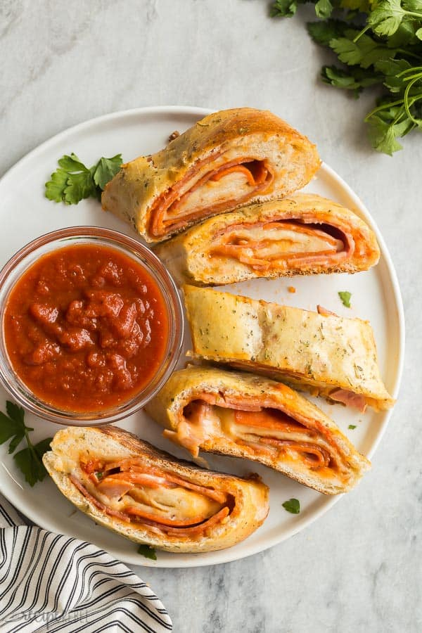 plate of sliced stromboli with pizza sauce