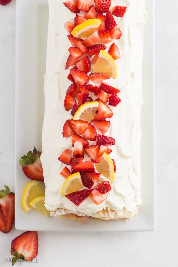 strawberry lemon cake roll overhead whole before slicing with fresh strawberries and lemon wedges on top