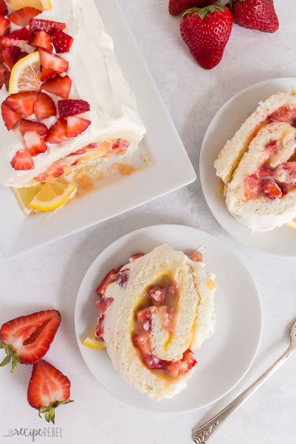 strawberry lemon angel food cake roll overhead with two slices on white plates and a fresh strawberry
