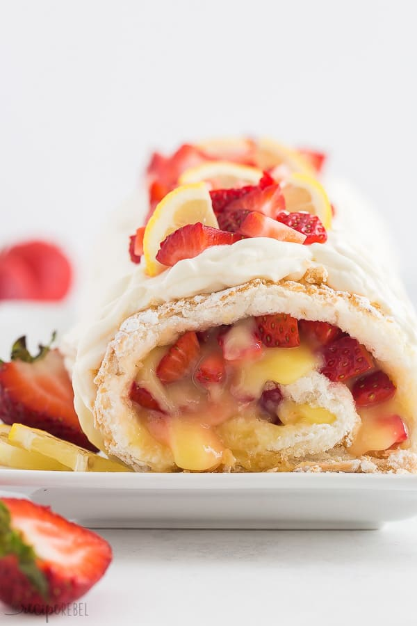 strawberry lemon cake roll close up with fresh strawberries and lemon wedges on top