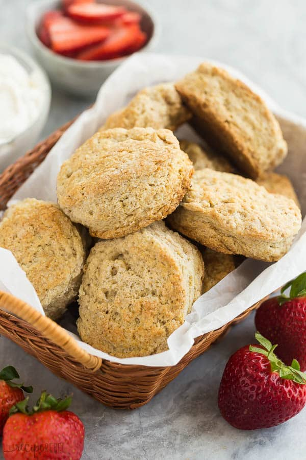 strawberry shortcake biscuits in a basket with fresh strawberries in the background