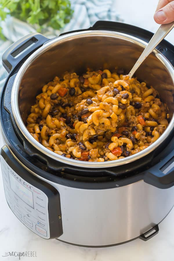 instant pot pasta with chili in pressure cooker being scooped in a metal spoon