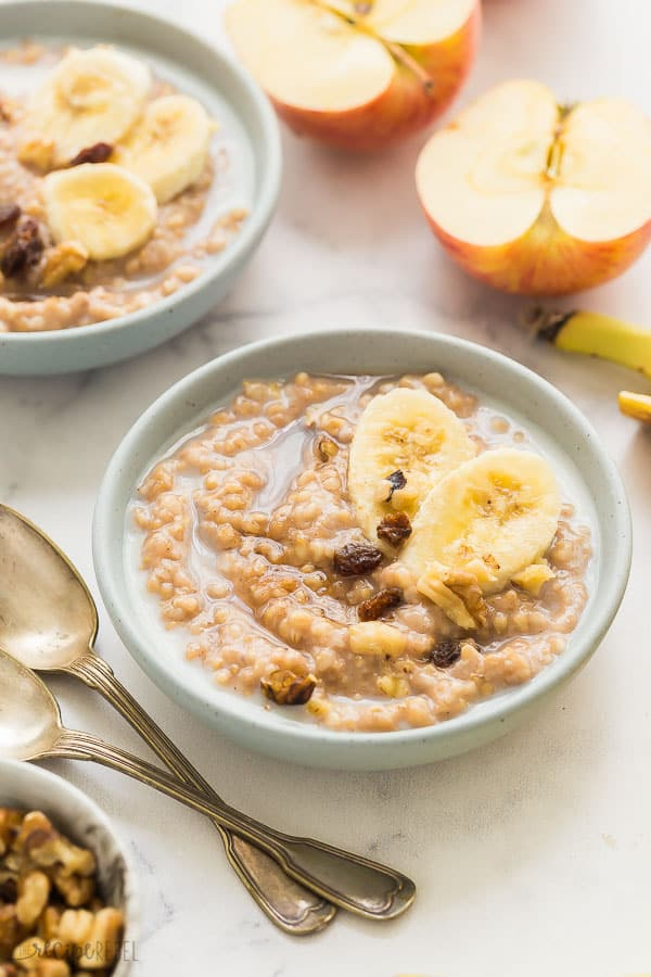 slow cooker oatmeal in blue bowls with banana and raisins and halved apple in the background