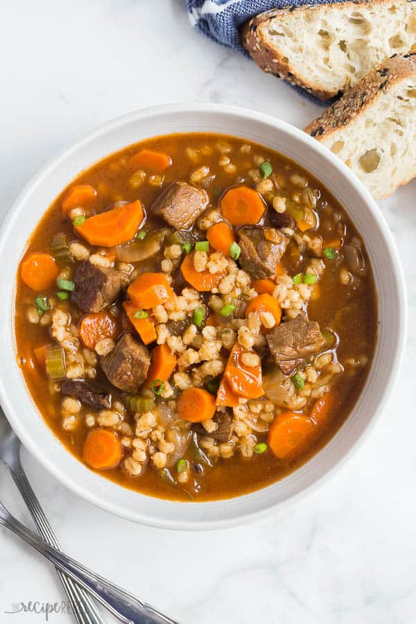 beef and barley soup in a white bowl overhead on white background