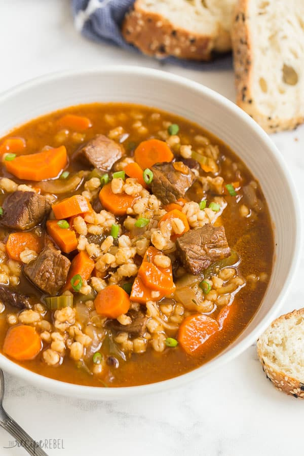 beef barley soup in bowl close up on white background with crusty bread